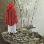 Little red riding hood on a shore of a misty lake