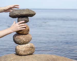 human hand making stack of large round stones near the water, which are due to the balance