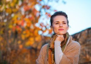 Portrait of thoughtful young woman standing in autumn outdoors in evening
